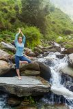 Woman in yoga asana Vrikshasana tree pose at waterfall outdoors Stock Images
