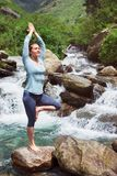 Woman in yoga asana Vrikshasana tree pose at waterfall outdoors stock photo