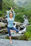 Woman in yoga asana Vrikshasana tree pose at waterfall outdoors Stock Photos