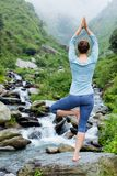 Woman in yoga asana Vrikshasana tree pose at waterfall outdoors Stock Image