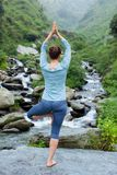 Woman in yoga asana Vrikshasana tree pose at waterfall outdoors Royalty Free Stock Photos