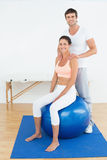 Woman on yoga ball working with physical therapist Stock Photography