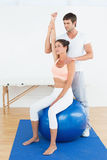 Woman on yoga ball working with physical therapist Stock Image