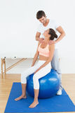 Woman on yoga ball working with physical therapist Royalty Free Stock Photo