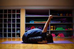 A woman, a yoga coach, makes incredible affairs and stretches Stock Photo