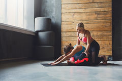 Woman with yoga instructor in class, asana cobbler pose. Yoga class instructor helps beginner to make asana exercises. Teacher assists to make cobbler pose royalty free stock images