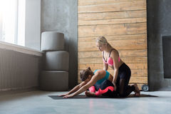 Woman with yoga instructor in class, asana cobbler pose. Yoga class instructor helps beginner to make asana exercises. Teacher assists to make cobbler pose royalty free stock image