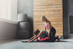 Woman with yoga instructor in class, asana cobbler pose. Yoga class instructor helps beginner to make asana exercises. Teacher assists to make cobbler pose stock images