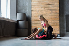 Woman with yoga instructor in class, asana cobbler pose. Yoga class instructor helps beginner to make asana exercises. Teacher assists to make cobbler pose royalty free stock photo