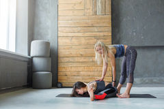 Woman with yoga instructor in class, asana cobbler pose. Yoga class teacher and beginner making asana exercises. Instructor assists to make cobbler pose, baddha royalty free stock photography