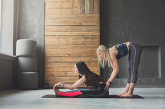 Woman with yoga instructor in class, asana cobbler pose. Yoga class teacher and beginner making asana exercises. Instructor assists to make cobbler pose, baddha stock photos