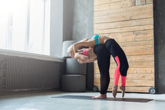 Woman with yoga instructor in class, back stretching Royalty Free Stock Images