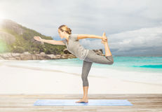 Woman in yoga lord of the dance pose on beach Royalty Free Stock Photo