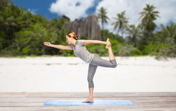 Woman in yoga lord of the dance pose on beach Stock Photos