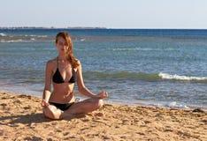 Woman in yoga lotus meditation back to seaside. Silhouette of woman in yoga lotus meditation position back to seaside Stock Photo