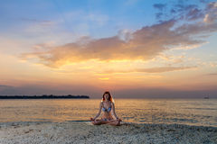 Woman in yoga lotus meditation at sunset. Woman in yoga lotus meditation position back to seaside at sunset Stock Photography