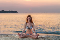 Woman in yoga lotus meditation at sunset Stock Photos
