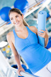 Woman with a yoga mat Royalty Free Stock Photos