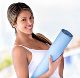 Woman with a yoga mat Royalty Free Stock Photo