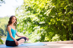 Woman on a yoga mat to relax. Royalty Free Stock Photos