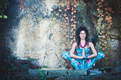 Woman in yoga meditation outdoor. Young woman in yoga meditation outdoor shot in front rock with autumn leaves Royalty Free Stock Photography