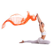 Woman in yoga pigeon pose and orange flying fabric Stock Photography