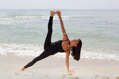 Woman in a yoga pose on the beach Royalty Free Stock Photography
