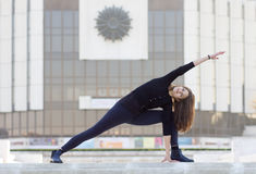 Woman in yoga pose in city. Woman in yoga position outside in urban setting stock images