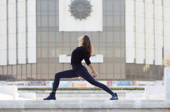 Woman in yoga pose in city. Woman in yoga position outside in urban setting Royalty Free Stock Photos
