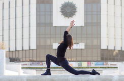 Woman in yoga pose in city. Woman in yoga position outside in urban setting royalty free stock photo