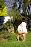 Woman in yoga pose in garden. Flexible young woman putting head between legs during yoga exercise in garden Royalty Free Stock Photos