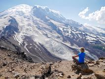 Woman in yoga pose meditating with ice covered mountain view. Stock Photos