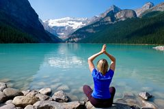 Woman in yoga pose meditating by water. Royalty Free Stock Photography