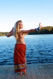 Woman in yoga pose outdoor. Lovely female in yoga pose on an outdoor lake setting Stock Photo