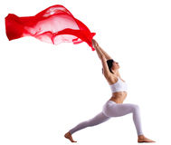 Woman in yoga pose with red flying fabric Royalty Free Stock Images