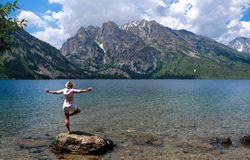 Woman in yoga pose standing by lake with mountain view. stock photography