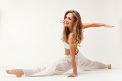Woman in yoga pose in studio on white background Royalty Free Stock Photography