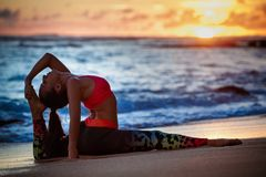 Woman in yoga pose on sunset sea beach Royalty Free Stock Photography