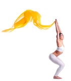 Woman in yoga pose and yellow flying fabric Stock Images