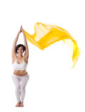 Woman in yoga pose and yellow flying fabric Stock Photography