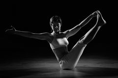 Woman in yoga position. Attractive young woman in yoga position with black background. Black and white photo Royalty Free Stock Photo