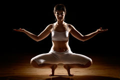 Woman in yoga position. Attractive young woman in yoga position with dark shadowy background Stock Photo