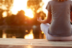 Yoga near water at sunset- body part Stock Photography