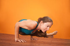 Woman In Yoga Posture. Young fit woman in yogasana posture over orange background Stock Image