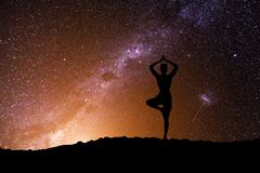 The woman with yoga posture on the mountain at night. The woman with yoga posture on the mountain on Milky Way background Royalty Free Stock Photos