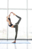 Woman yoga practice exercises pose training concept on window city background in gym hall Stock Image