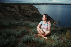 Woman Yoga - relax in nature. Girl sitting near a cliff, doing sports Stock Image