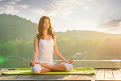 Woman Yoga - relax in nature on the lake.  royalty free stock photo