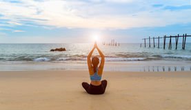 Woman yoga on the sea beach Stock Photo