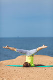Woman yoga. Series. Outdoor. On the seashore. Healthy woman resting and curl up in fetal position outdoor at the sea: yoga pose. Series stock photography